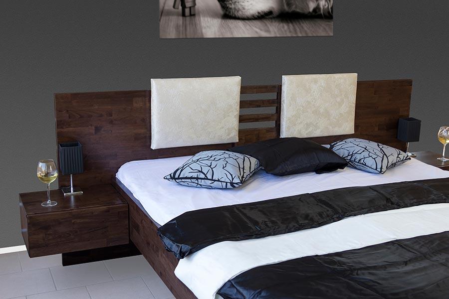 Masivní postel NEVE nabízí zajímavé řešení uchycení nočních stolků v kombinaci s čalouněnými polštáři na dlouhém a masivním čele u hlavy.