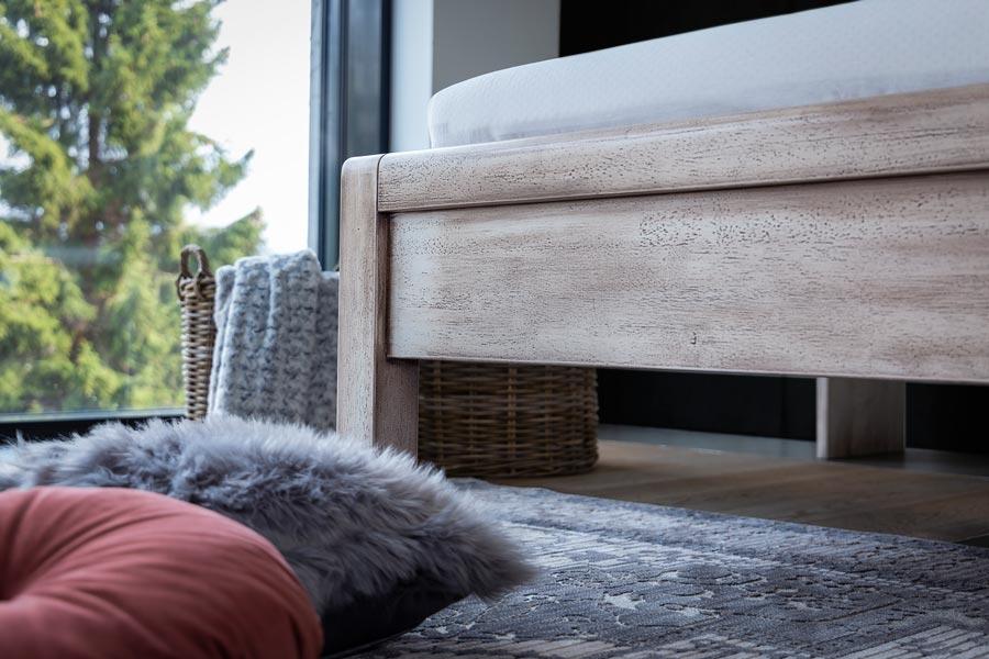 Detail čela u nohou na luxusní masivní posteli MONA s povrchovou úpravou patinováním. Postel je vyrobena z masivního rámu o síle 7 cm
