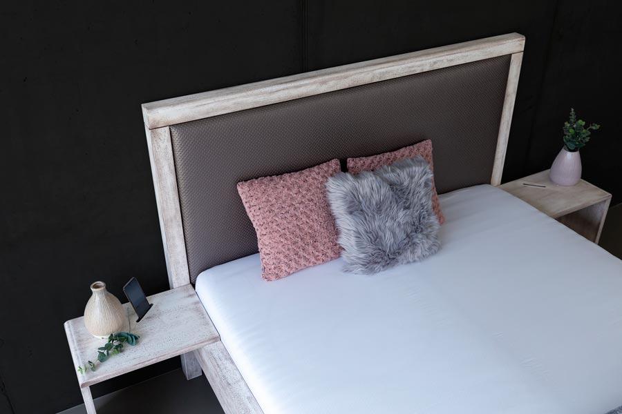 Pohled na čelo u hlavy a detail stolků u luxusní masivní postele MONA. V detailu je vidět vysoké čelo a luxusní čalounění, doplněné o novou povrchovou úpravu patinováním.