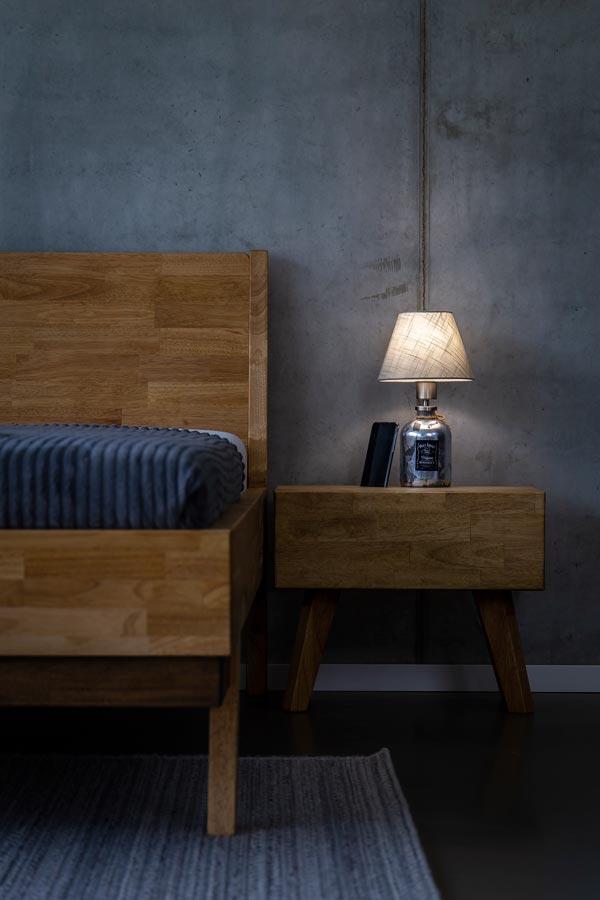 Noční stolek pro postel z masivu JESSIE má drážku, do které lze pohodlně postavit mobilní telefon.